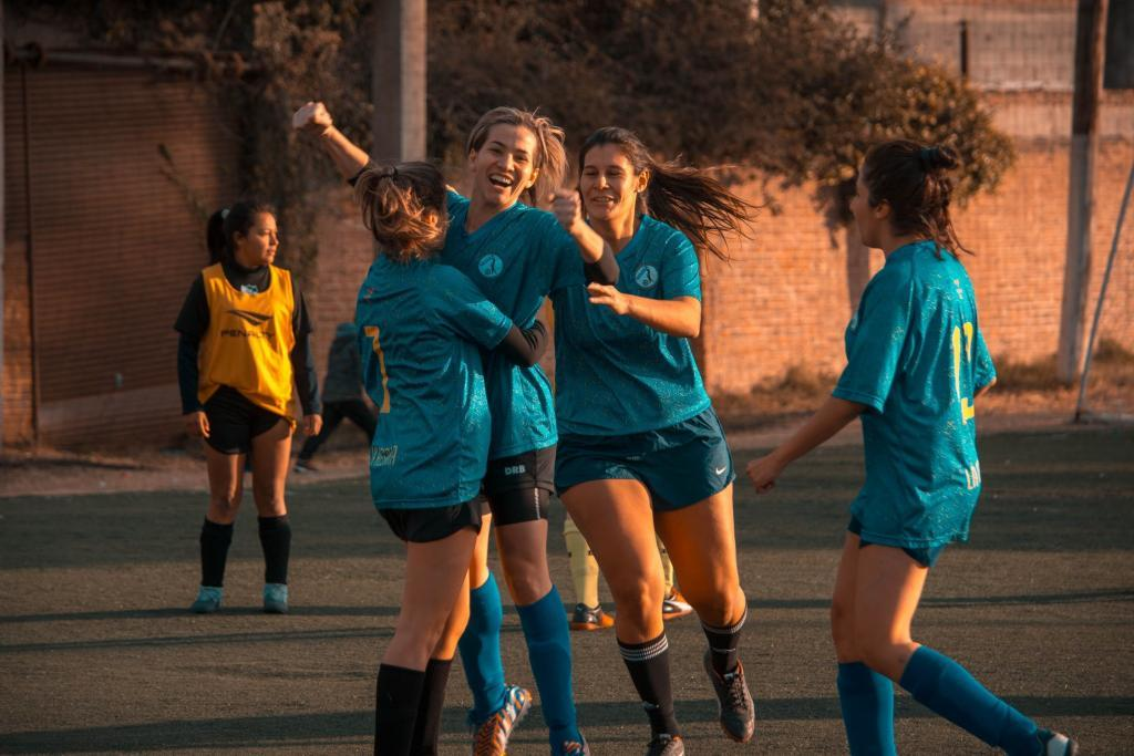 Four girls embracing during a soccer game
