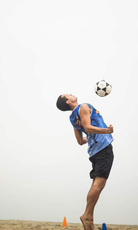 Man practicing a soccer trick on the beach