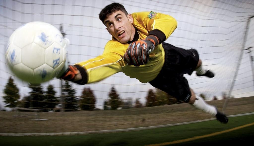 Male Goalie in Yellow shirt blocking a shot