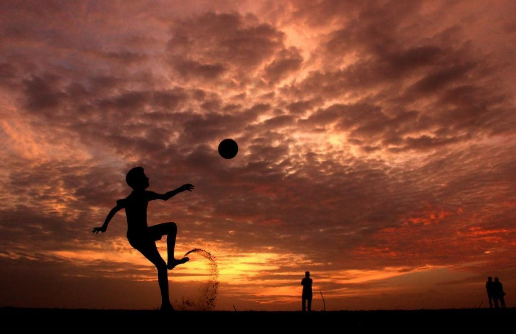Silhouette of a man practicing soccer skills